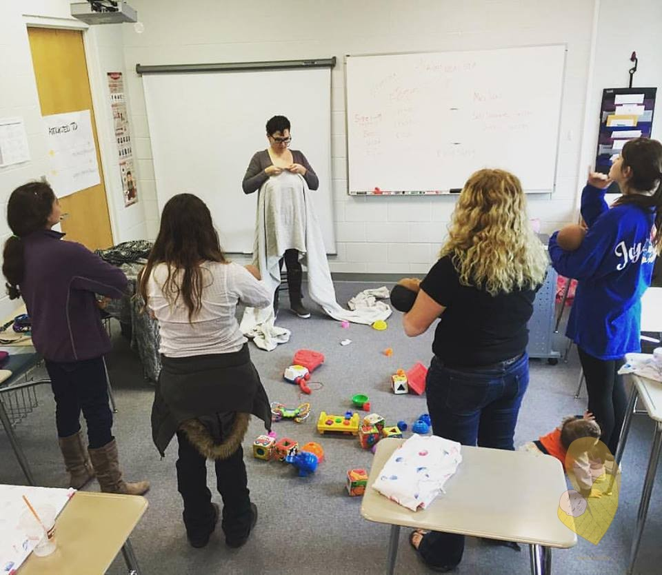 Fotografija: Elena stoji u učionici, držeći in a classroom holding a white/light grey long wrap at the middle marker as a class of 4 students watch on, holding baby dolls. Baby N is crawling and grabbing at one student's leg at the lower right of the picture.